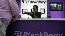 A salesman explains the features of a blackberry phone to a customer inside a showroom in Mumbai. (DANISH SIDDIQUI/REUTERS)