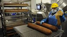 The production area at a Maple Leaf Foods plant. Here, a worker prepares large rolls of bologna for automated slicing. (Fred Lum/The Globe and Mail)