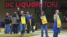 Striking B.C. Government and Service Employees' Union worker wave at passing vehicles at the liquor distribution branch on East Broadway in Vancouver on July 3, 2012. (Jeff Vinnick For The Globe and Mail)