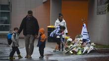 A girl lays a a bouquet of flowers at the memorial for Julie Paskall outside the Newton Arena in Surrey, B.C., Jan. 2, 2013. (Ben Nelms for The Globe & Mail)