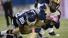 Winnipeg Blue Bombers' Aaron Kelly, 19, is stopped by Toronto Argonauts' Pat Watkins during first quarter CFL action in Toronto on Thursday Oct. 24, 2013. (FRANK GUNN/THE CANADIAN PRESS)