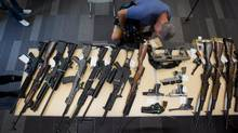 A television cameraman records video of ammunition sitting on the floor as some of the firearms seized from a man arrested in Tatla Lake, B.C., are displayed during a news conference at RCMP headquarters in Surrey, B.C., on Aug. 29, 2013. (Darryl Dyck for The Globe and Mail)