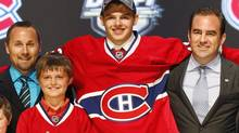 Alex Galchenyuk, center, smiles with officials from the Montreal Canadiens after being chosen third overall in the first round of the NHL draft on Friday, June 22, 2012, in Pittsburgh. (Keith Srakocic/AP)
