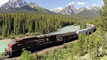 A CPR (Canadian Pacific Railway) freight train runs along the Bow River and distant Rocky Mountains on the CPR main line near Lake Louise, Alberta. The Canadian Press Images/Larry MacDougal (LARRY MACDOUGAL/The Canadian Press Images/LARRY MACDOUGAL/The Canadian Press Images)