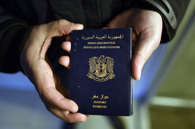 Narsis Bardakjian holds his Syrian passport while waiting to move into his new home in Canada on Dec. 23, 2015.