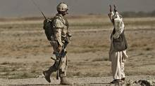 An Afghan man lifts up his arms as a soldier with the the Royal Canadian Regiment approaches him during a patrol in the Panjwaii district, southwest of Kandahar, Afghanistan, on Sept. 9, 2010. (Anja Niedringhaus/AP)