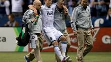 Vancouver Whitecaps captain Jay DeMerit is carried off the field after being injured during the first half of an MLS soccer game against Toronto FC in Vancouver, B.C., on Saturday March 2, 2013. DeMerrit is expected to miss most of the season after undergoing surgery to repair a ruptured Achilles tendon. (DARRYL DYCK/THE CANADIAN PRESS)