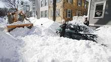 A Boston snow machine operator informs a couple that they will need to shovel their car out all over again after he clears the snow from their unplowed street in Boston Sunday, Feb. 10, 2013. (Winslow Townson/AP)