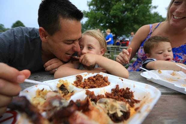 The Ugarte clan including dad, Juande, daughter, Skyanne, 3.5 baby, Ethan and mom, Ashley enjoy their rib dinners at the St. Thomas, Ribfest on Saturday July 25, 2015.