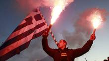 A firefighter raises flares as he protests in front of the parliament in Athens. Policemen, firefighters and coast guards protested on Tuesday against planned wage and pension cuts. (Kolesidis/Reuters)
