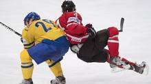 Team Canada Taylor Hall and Sweden's Erik Gustafsson collide during third period preliminary round action Thursday, May 9, 2013 at the world hockey championship in Stockholm Sweden. (The Canadian Press)