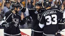 Los Angeles Kings players Justin Williams (14) , Willie Mitchell (33) and Justin Williams (14) celebrate after a goal by Dwight King (not pictured) against the New York Rangers in the third period during Game 2 of the 2014 Stanley Cup Final at Staples Center. (USA TODAY Sports)