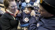 Meghan and Brady Simpson dress their son Blake in a new Winnipeg Jets jersey and hat. Jets fans are among the most loyal in the NHL, but everywhere, it seems, fans are happy to have hockey back. (JOHN WOODS/GLOBE AND MAIL)