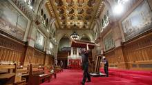 A worker carries a bench while preparing the Senate chamber on Parliament Hill in Ottawa on Oct. 10, 2013. (CHRIS WATTIE/REUTERS)