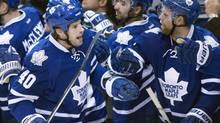 Toronto Maple Leafs winger Troy Bodie (40) is congratulated by teammates Nazem Kadri (centre) and Phil Kessel (right) after scoring on Phoenix Coyotes goaltender Mike Smith during first period NHL action in Toronto on Thursday December 19, 2013. (Frank Gunn/THE CANADIAN PRESS)