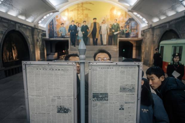 Commuters angle for a view of the day's state newspaper while they wait for their subway train in Puhung Station. Though smartphones with access to North Korea's self-contained intranet do exist, their cost puts them out of reach to all but a privileged few, and newspapers are the most common way of staying connected.