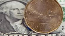 A Canadian dollar, or loonie, sits on top of its American counterpart. (Adrian Wyld/The Canadian Press)