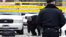 A member of the Special Investigations Unit inspects a used shell casing after a man was fatally shot by the police after allegedly threatening officers with scissors in Toronto on Feb. 3, 2012. (Chris Young For The Globe and Mail/Chris Young For The Globe and Mail)