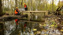 Scientists install and program a surface-water sampler on Spencer Creek, just downstream from the Valens Reservoir near Cambridge, Ont. (Peter Power/The Globe and Mail)