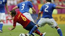 Italy's Giorgio Chiellini (C) fouls Spain's Andres Iniesta (L) as Italy's Christian Maggio (R) challenges, resulting in a yellow card for Chiellini, during their Group C Euro 2012 soccer match at the PGE Arena in Gdansk, June 10, 2012. (JUAN MEDINA/REUTERS)