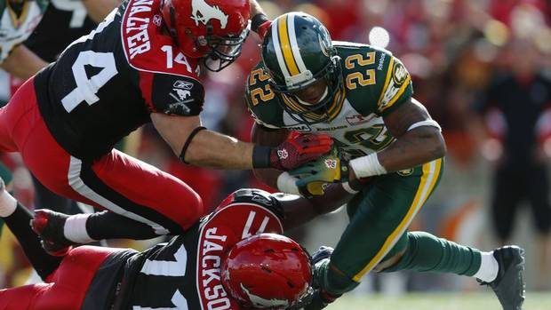Calgary Stampeders Matt Walter (14) and teammate Malik Jackson (11) tackle Edmonton Eskimos Joe Burnett during the second half of their CFL football game in Calgary, Alberta, September 3, 2012. (TODD KOROL/REUTERS)