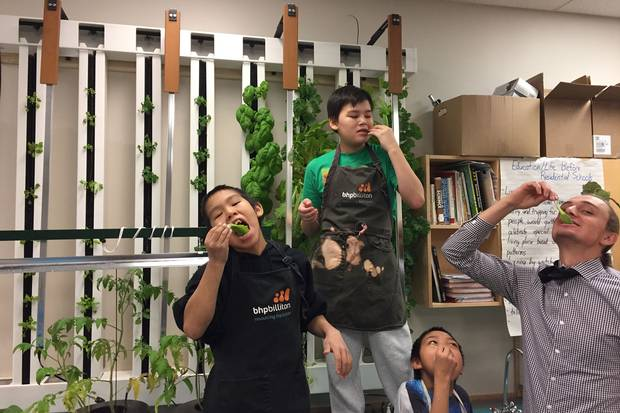 Students and teacher Michael Valk enjoy the leafy greens they've grown in their plant towers at Kugluktuk High School in Nunavut.