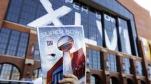 A vendor sells program books for the NFL Super Bowl XLVI football game between the New England Patriots and the New York Giants outside of Lucas Oil Stadium, Sunday in Indianapolis. (Michael Conroy)