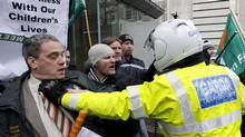 A motorbike police officer holds back Sinn Fein protesters who broke through the gates at government buildings, Dublin, Ireland. The Sinn Fein protesters were calling for the Irish Prime Minister to resign. Ireland's banks will be pruned down, merged or sold as part of a massive EU-IMF bailout, the government says as a shellshocked nation comes to grips with its failure to protect its financial institutions. (Peter Morrison/Peter Morrison/AP)