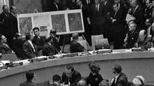 U.S. Ambassador Adlai Stevenson, seated at right, describes aerial photographs of launching sites for intermediate range missiles in Cuba during an emergency session of the United Nations Security Council Oct. 25, 1962, at the height of the Cuban Missile Crisis. (AP)