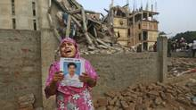 A Bangladeshi woman holds a picture of her missing husband at the crumbled building in Savar. (Kevin Frayer/AP)