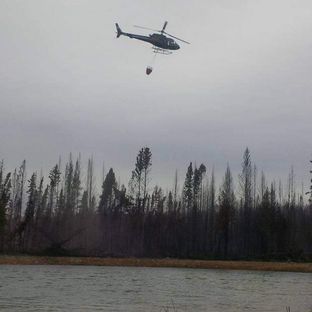 Ken Saumure, a pilot with Phoenix Heli-Flight, fills a bucket with water to douse a hotspot near the company's hangers and fuel tanks.