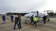 Staff from Devon Energy load a North Cariboo Aircraft at the company's modernized airport near Conklin, Alta. (Todd Korol/Todd Korol for The Globe and Mail)