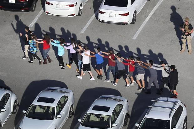 Feb. 14, 2018: People are brought out of Marjory Stoneman Douglas High School in Parkland, Fla., after a shooting at the school.