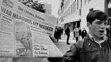 A newsboy holds up a newspaper with a banner headline reporting the invoking of the War Measures Act on Oct 16, 1970, following the kidnapping of British diplomat James Cross and Quebec Labour Minister Pierre Laporte by the FLQ. (CP)