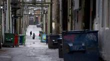 People walk through a back alley in the downtown eastside area of Vancouver, December, 23, 2012. Police say 21 per cent of their calls involve someone who is mentally ill, and apprehensions under the Mental Health Act have risen 16 per cent between 2010 and 2012. (JONATHAN HAYWARD/THE CANADIAN PRESS)