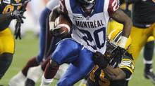 Montreal Alouettes' Victor Anderson (L) is caught by Edmonton Eskimos' Damaso Munoz during their CFL game in Edmonton August 17, 2012. (DAN RIEDLHUBER/REUTERS)