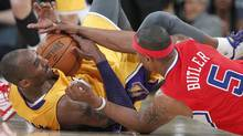 Los Angeles Clippers' Caron Butler (5) and Los Angeles Lakers' Kobe Bryant scramble for the ball on the court during their NBA preseason basketball game in Los Angeles, California December 19, 2011. REUTERS/Lucy Nicholson (Lucy Nicholson/Reuters)