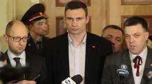Ukrainian opposition leaders Arseniy Yatsenyuk, left, Vitali Klitschko, middle, and Oleh Tyahnybok face the media, during a briefing in the Ukrainian parliament in Kiev, Ukraine, Wednesday, Jan. 29, 2014. Ukraine's parliament has passed a measure offering amnesty to arrested protesters, but only if demonstrators vacate most of the buildings they occupy. The measure, passed on Wednesday after nearly 12 hours of negotiation, was not supported by the opposition parties driving the two months of protests that pushed the country into crisis. (Sergei Chuzavkov/AP)