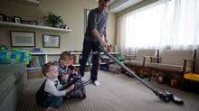 Richard Abgrall vacuums as his twin three-year-old sons Mason Mehnert, left, and Declan Mehnert try to help at their home in Vancouver. (DARRYL DYCK FOR THE GLOBE AND MAIL)