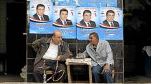 An Egyptian smokes water pipe in front of election campaign banners at a cafe in Cairo Nov. 27, 2011. (Ahmed Jadallah/Reuters/Ahmed Jadallah/Reuters)