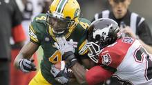 Edmonton Eskimos' Adarius Bowman is force out of bounds by Calgary Stampeders' Brandon Smith during their CFL football game in Edmonton July 24, 2014. (DAN RIEDLHUBER/REUTERS)