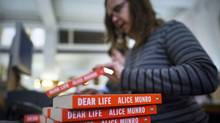 A seller handles Alice Munro books at the Munro's Books in Victoria October 10, 2013. Ms. Munro has been named the winner of the Nobel Prize for Literature, making her the first Canadian to win the honour. (John Lehmann/The Globe and Mail)