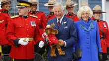Britain's Prince Charles holds a stuffed toy moose beside his wife Camilla, Duchess of Cornwall and RCMP officers in Pictou, Nova Scotia, May 19, 2014. (MARK BLINCH/REUTERS)