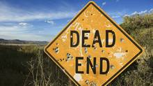 Dead end sign with bullet holes. (Ron Chapple/www.jupiterimages.com)