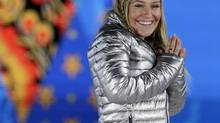 Gold medalist in the women's snowboard slopestyle Jamie Anderson of the United States smiles during the medals ceremony at the 2014 Winter Olympics, Sunday, Feb. 9, 2014, in Sochi, Russia. 'Tinder in the Olympic Village is next level,' she says (Morry Gash/AP)