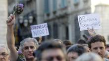 People hold signs as they protest at Sant Jaume square in central Barcelona June 17, 2012. (ALBERT GEA/REUTERS)