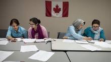 Immigrants from Afghanistan take part in a Canadian citizenship class lat June at the Afghan Women's Organization in Toronto. (Moe Doiron/The Globe and Mail)