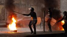 Riot police walk past a burning barricade during clashes in Cairo January 26, 2011. Thousands of Egyptians defied a ban on protests by returning to Egypt's streets on Wednesday and calling for President Hosni Mubarak to leave office, and some scuffled with police. (GORAN TOMASEVIC/REUTERS/Goran Tomasevic)