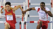 Cuba's Dayron Robles, right, makes contact with China's Liu Xiang, left, during the men's 110m hurdles final at the World Athletics Championships in Daegu, South Korea, Monday. (Martin Meissner/Associated Press)