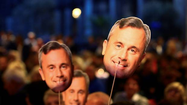 Hofer supporters hold masks with his face on them during the 'FPOe Summer Party' in Vienna on Sept. 6, 2016.